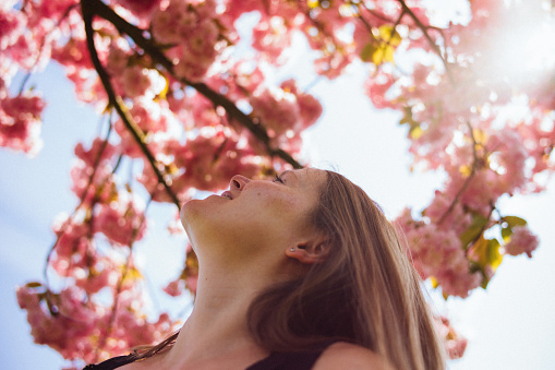 Smiling woman looking up to a blooming tree. - gettyimageskorea