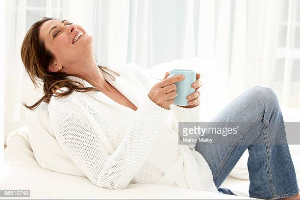 smiling woman lounging with a blue coffee mug. - 頭をそらす ストックフォトと画像