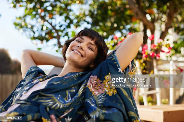 smiling woman lying back in a deck chair on her patio - deck chair stock pictures, royalty-free photos & images
