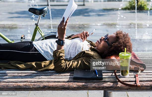 Smiling woman lying on a bench reading notes