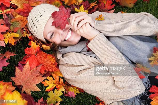 Lächelnde Frau auf Herbst liegen lässt