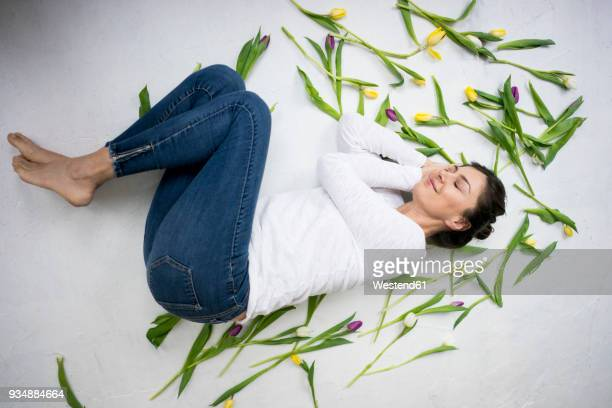 Smiling woman lying on floor amidst tulips