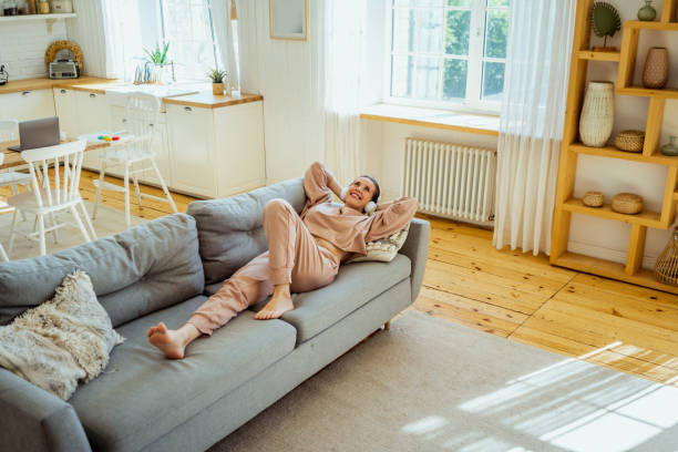 Smiling woman lying on sofa while contemplating at home