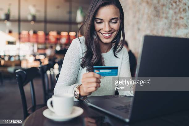 smiling woman making a credit card purchase - credit card stock pictures, royalty-free photos & images