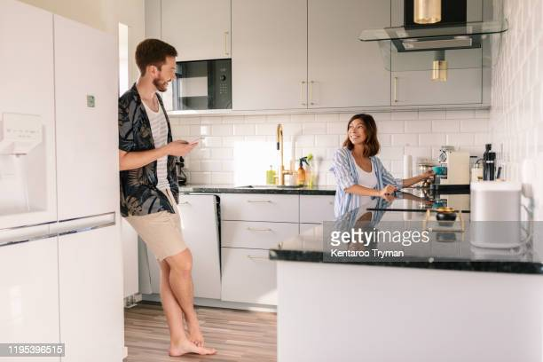 smiling woman making coffee while looking at man using phone in kitchen - relationship stockfoto's en -beelden