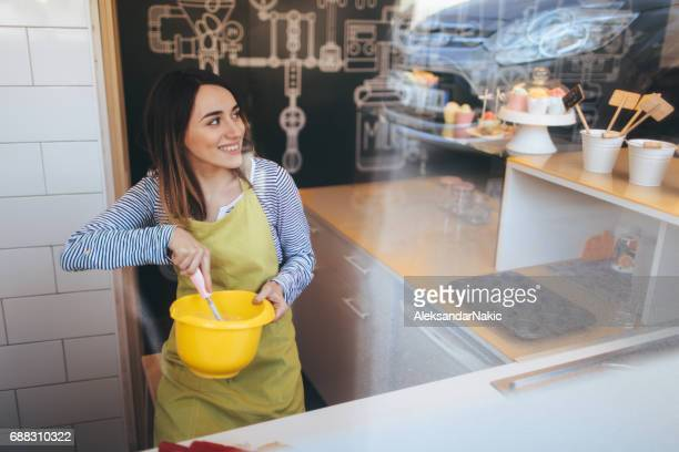 Smiling woman making delicious desserts in her cake shop