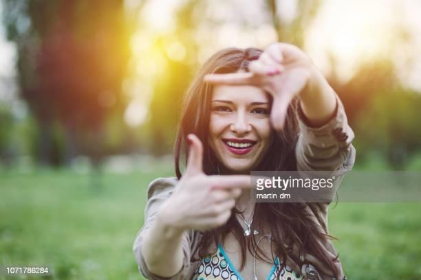 mulher sorridente fazer mão frame - dedos fazendo moldura - fotografias e filmes do acervo