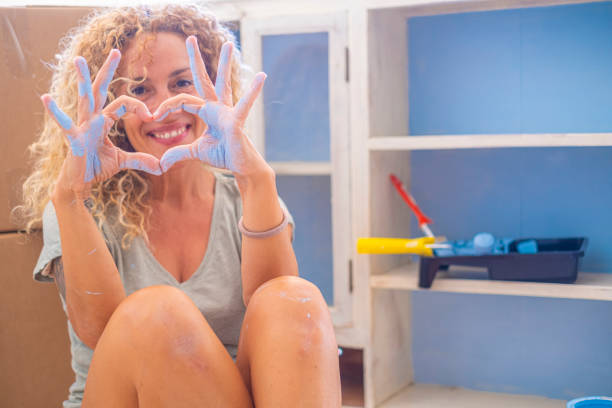 Smiling woman making heart from blue painted hands while renovating at home