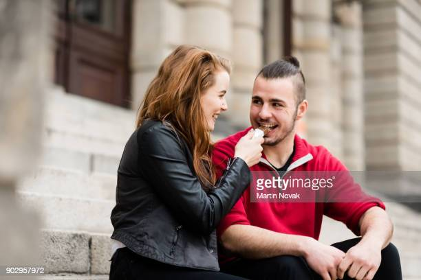 smiling woman making her man eat chocolate - couple chocolate stock pictures, royalty-free photos & images