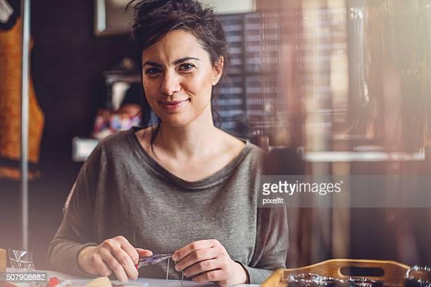 Smiling woman making jewelry