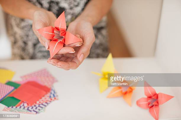 Smiling woman making origami flowers