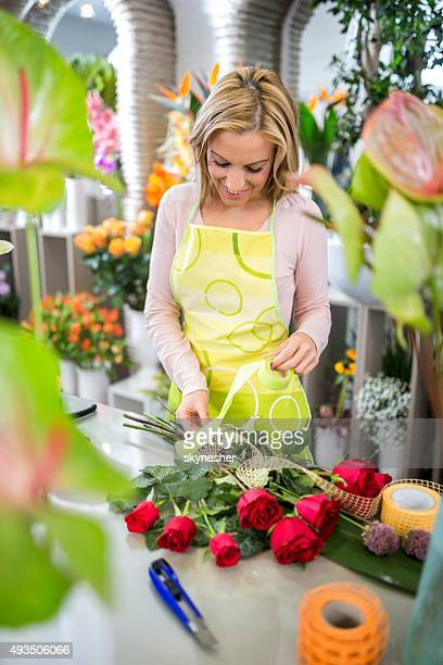 Smiling woman making rose bouquet in flower shop.