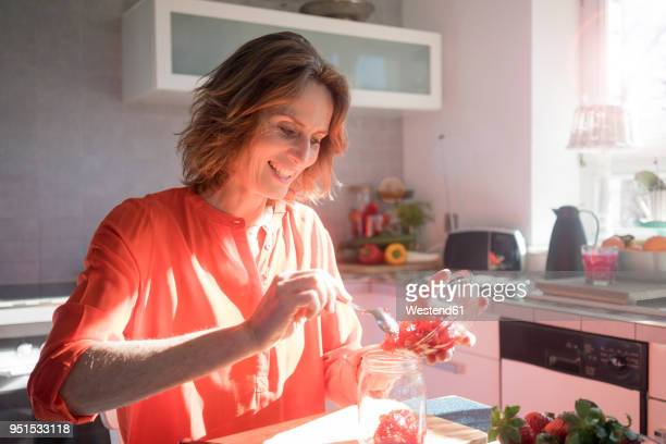 Smiling woman making strawberry jam in kitchen at home