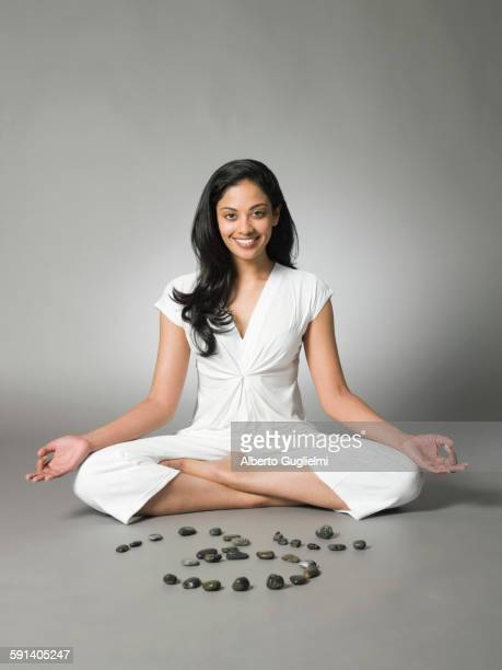 Smiling woman meditating by peace symbol in stones