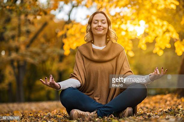 Smiling woman meditating in autumn day at the park.