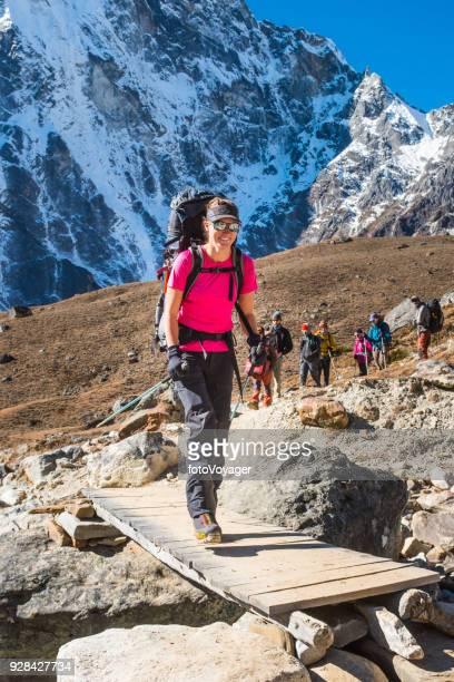 Smiling woman mountaineer hiking on Himalaya mountain trail Khumbu Nepal