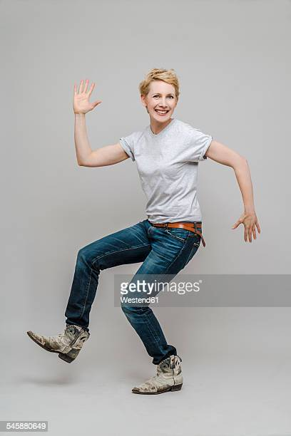 Smiling woman moving in front of grey background