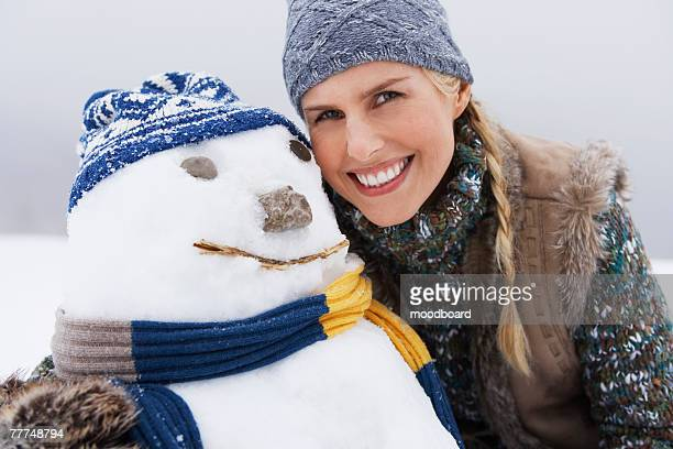 Smiling Woman Next to Snowman