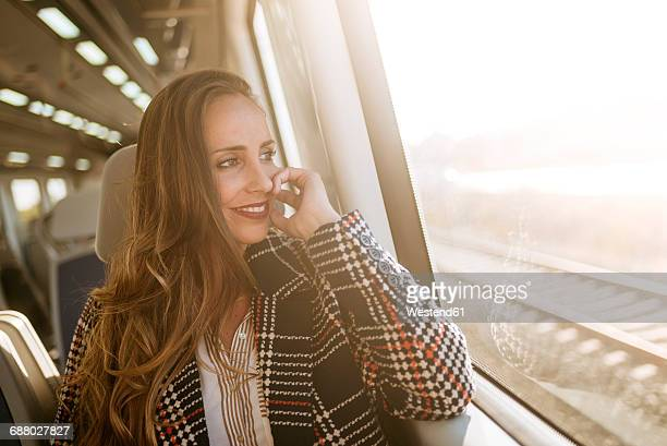 Smiling woman on a train looking out of window