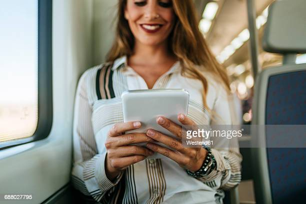 Smiling woman on a train using a tablet