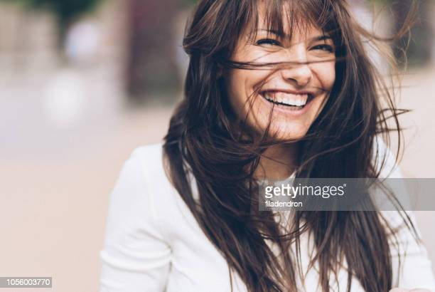 smiling woman on a windy day - brown hair stock pictures, royalty-free photos & images