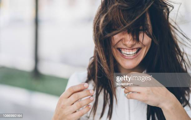 smiling woman on a windy day - imperfection stock pictures, royalty-free photos & images