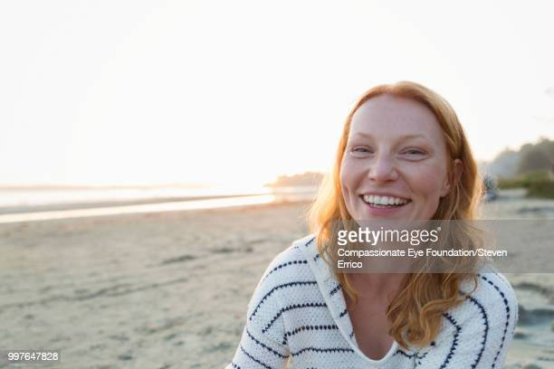 Smiling woman on beach at sunset