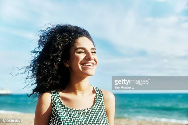 smiling woman on beach. - curly stock pictures, royalty-free photos & images
