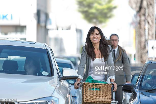 Smiling woman on bicycle in traffic jam