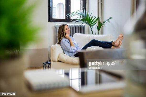 smiling woman on couch at home on the phone - donne bionde scalze foto e immagini stock