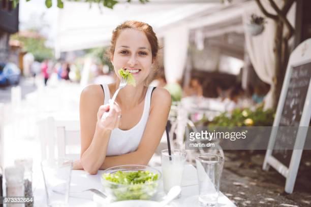 Leende kvinna på diet äta grön sallad i restaurang