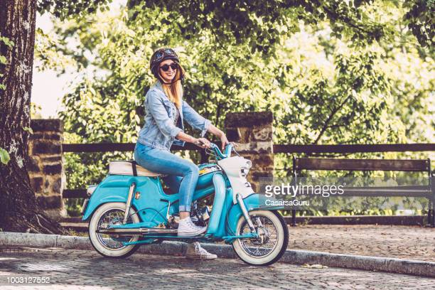 smiling woman on motor scooter stopping on the side of the road - moped stock photos and pictures