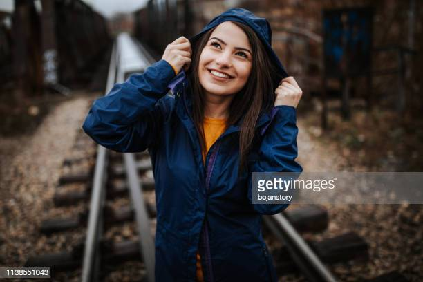 smiling woman on railway bridge - hood clothing stock pictures, royalty-free photos & images