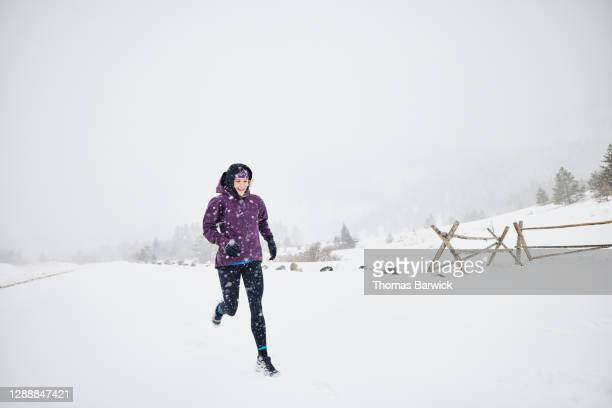smiling woman on run during blizzard - forward athlete stock pictures, royalty-free photos & images