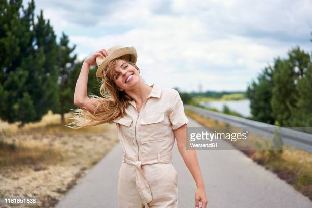 smiling woman on rural road at the lakeside - jumpsuit stock pictures, royalty-free photos & images