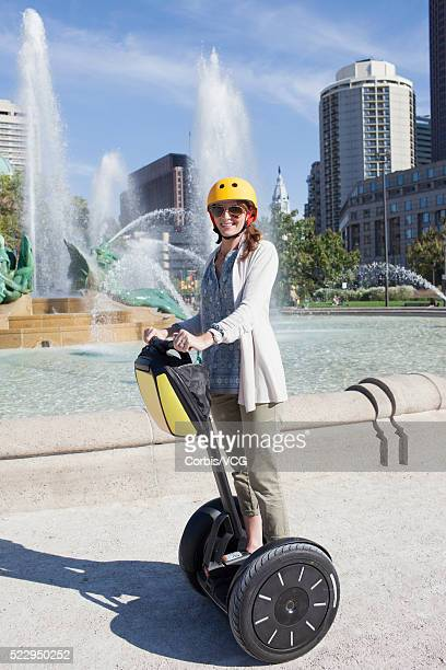 Smiling woman on segway with fountain on background, Philadelphia, Pennsylvania, USA