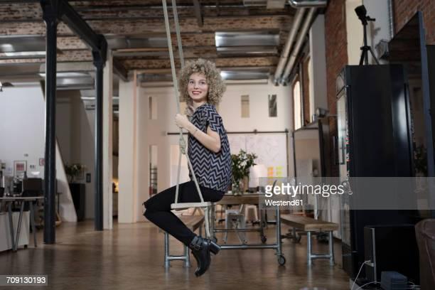Smiling woman on swing in modern office