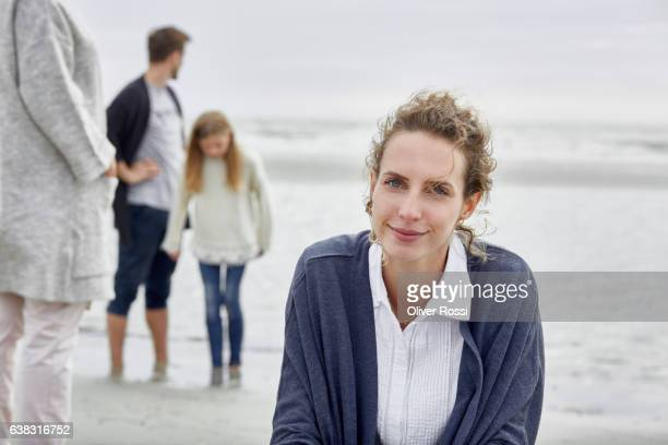 Smiling woman on the beach with family in background