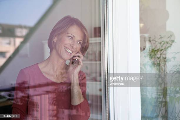 Smiling woman on the phone at the window
