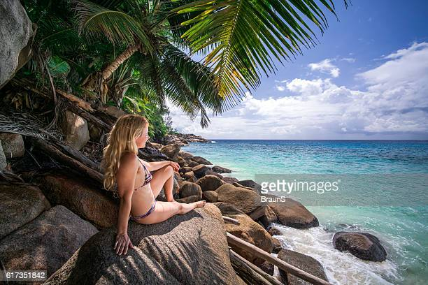 Smiling woman on the rocks enjoying a day at sea.