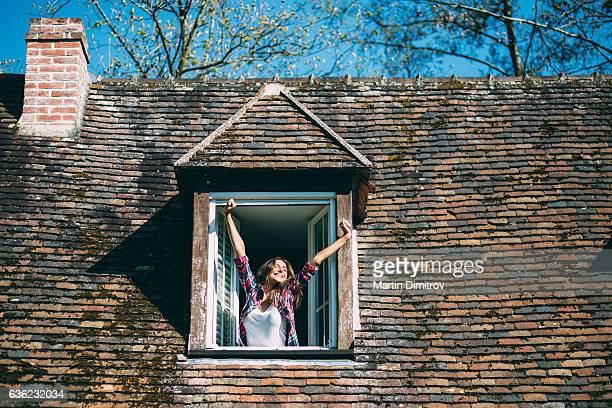 Smiling woman on the rooftop window
