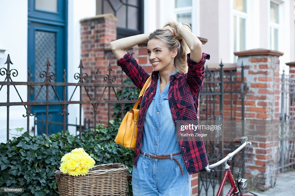 smiling woman on the street with her bicycle : Stock-Foto