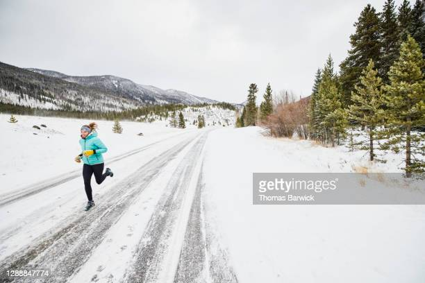 smiling woman on winter run on snowy road - forward athlete stock pictures, royalty-free photos & images