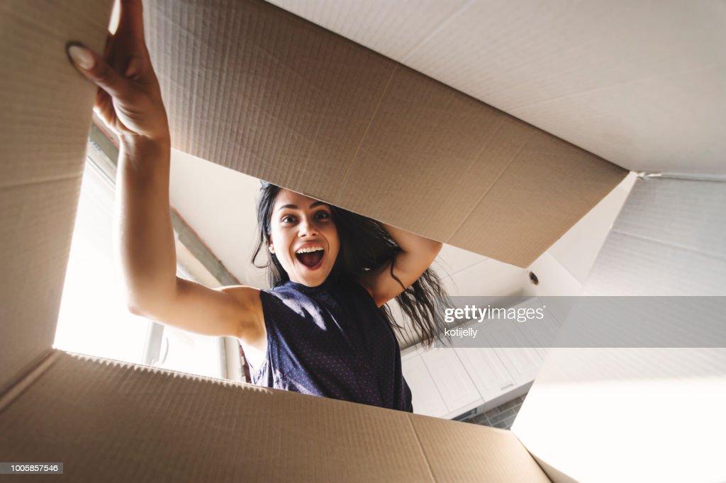 Mujer sonriente abrir una caja de cartón : Foto de stock