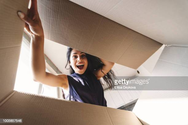 smiling woman opening a carton box - surprise stock pictures, royalty-free photos & images
