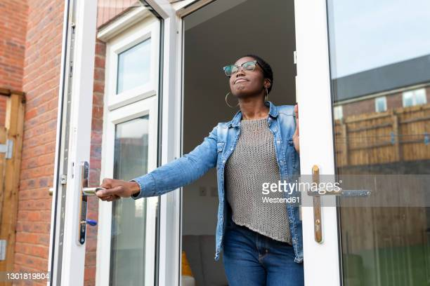 smiling woman opening house doors - door stock pictures, royalty-free photos & images