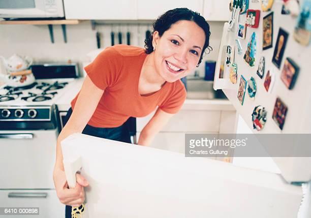Smiling Woman Opens Fridge