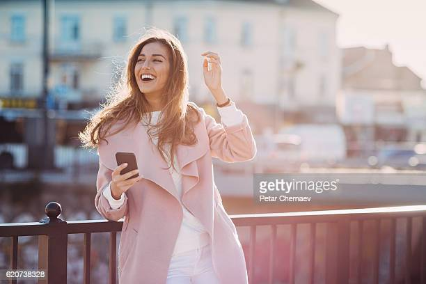 Smiling woman outdoors at sunlight