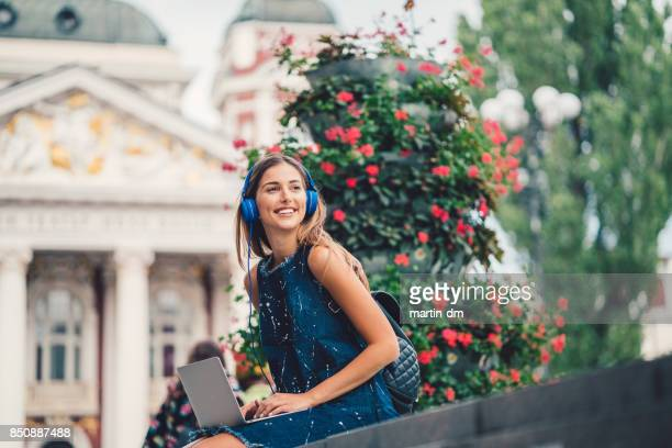Smiling woman outside using laptop and listening to podcasts