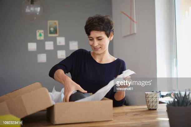 smiling woman packing parcel at home - unpacking stock pictures, royalty-free photos & images